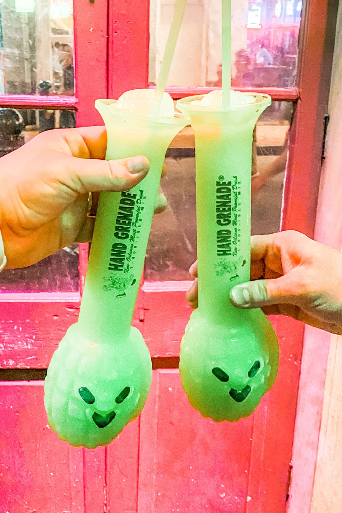 Bright green drinks in front of a pink door in New Orleans