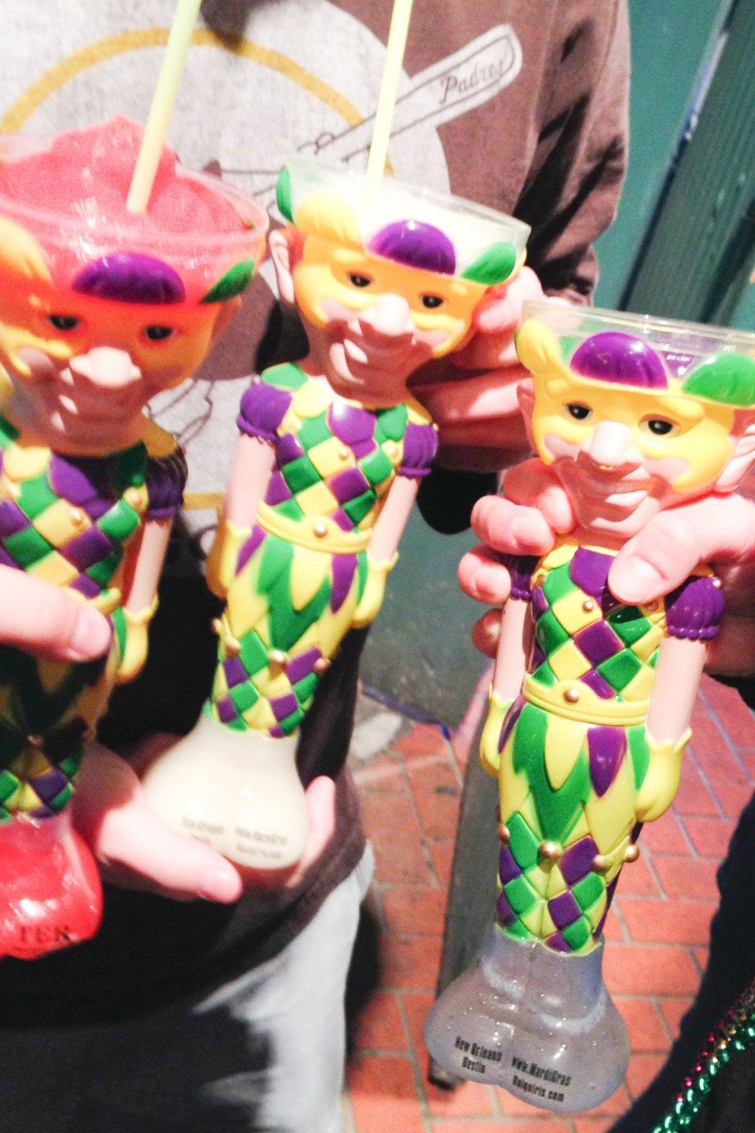Colorful jester drinks in front of pink door