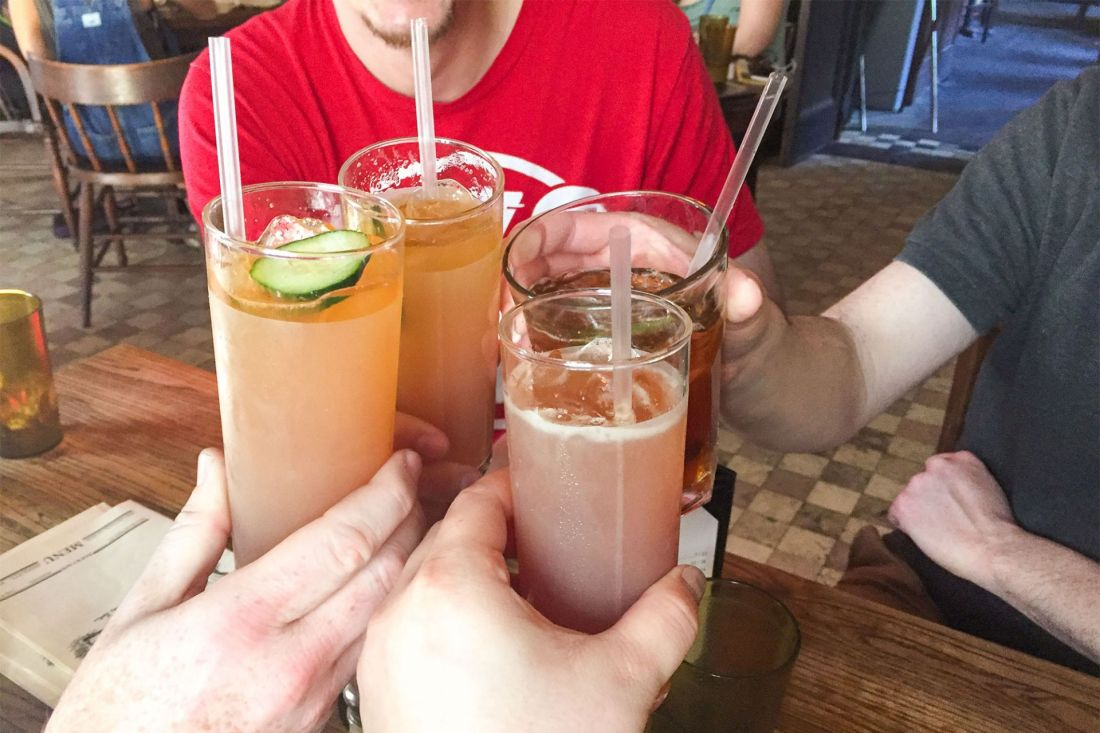 Friends toasting tall cocktails with garnishes
