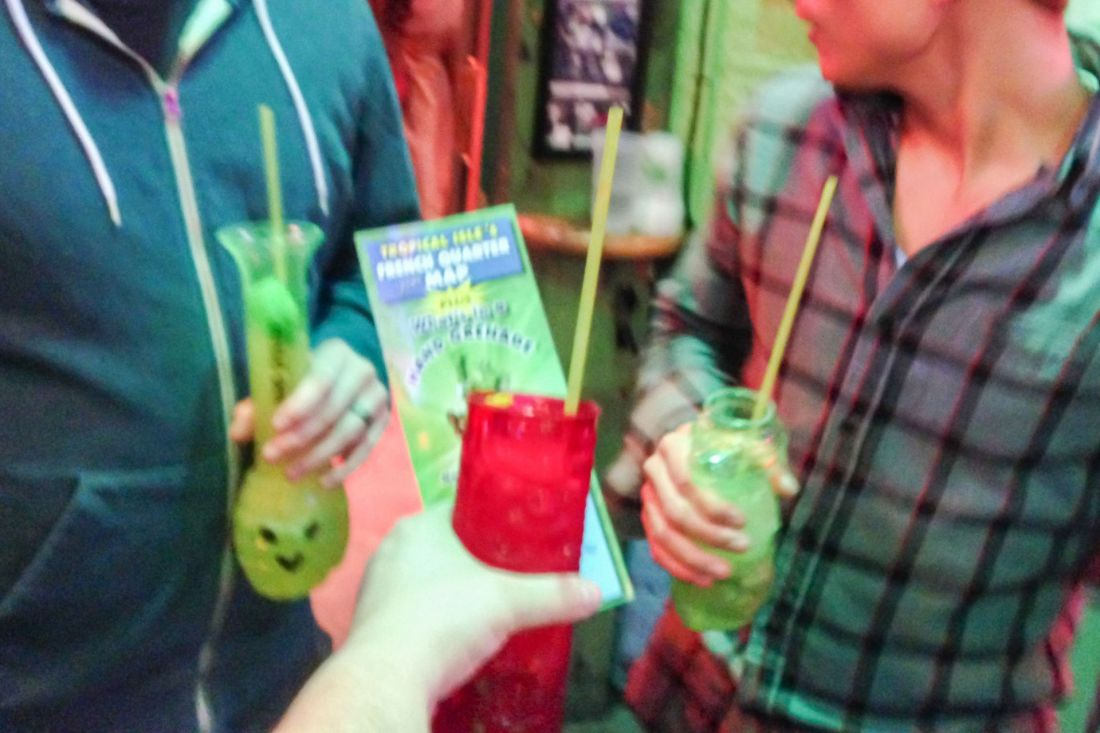 Green and red drinks with two males and female holding