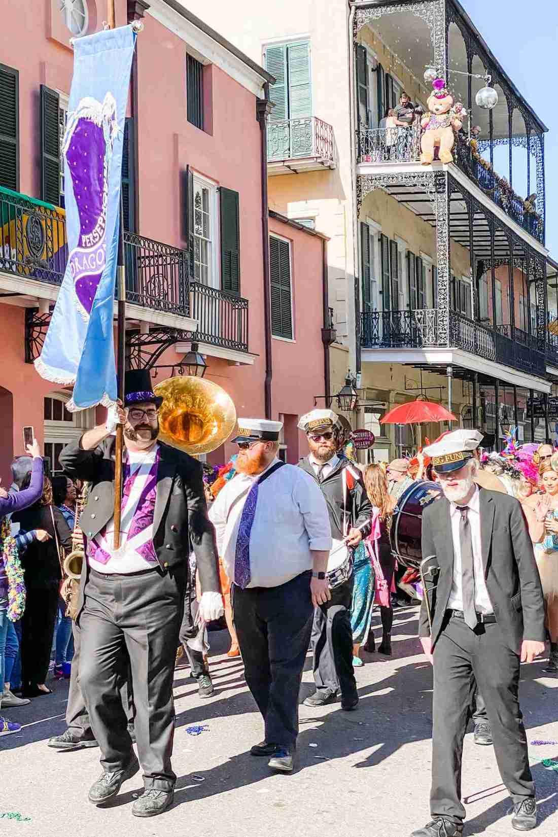 Older men walk down street playing instruments