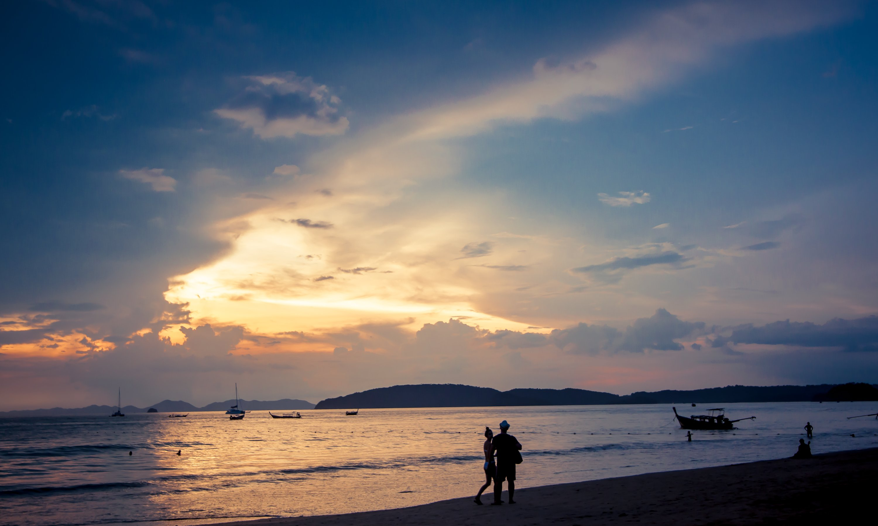 A silhouetted couple walking on Ao Nang Beach Krabi Thailand
