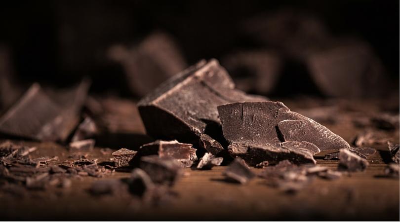Broken bars of gourmet chocolate with scattered shavings