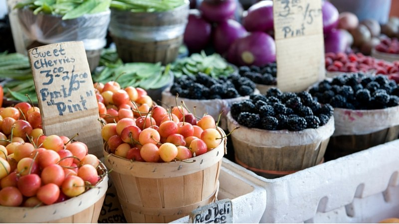 baskets of cherries and berries on sale at a farmer's market