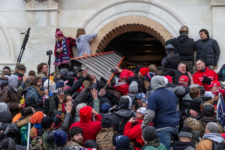 capitol rioters shove a ladder through a window