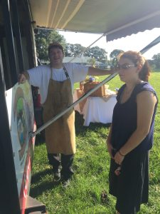 LoSU school founder's daughter talking with Chris of Piedmont Smokehouse.