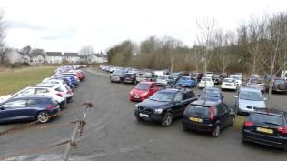 A busy car park with the walkathon on a sunny day