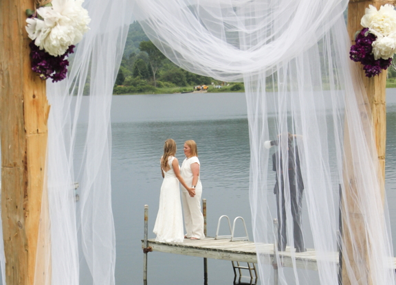 Two brides at country wedding beside lake