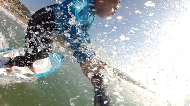 Bottom turn with spray from paddle