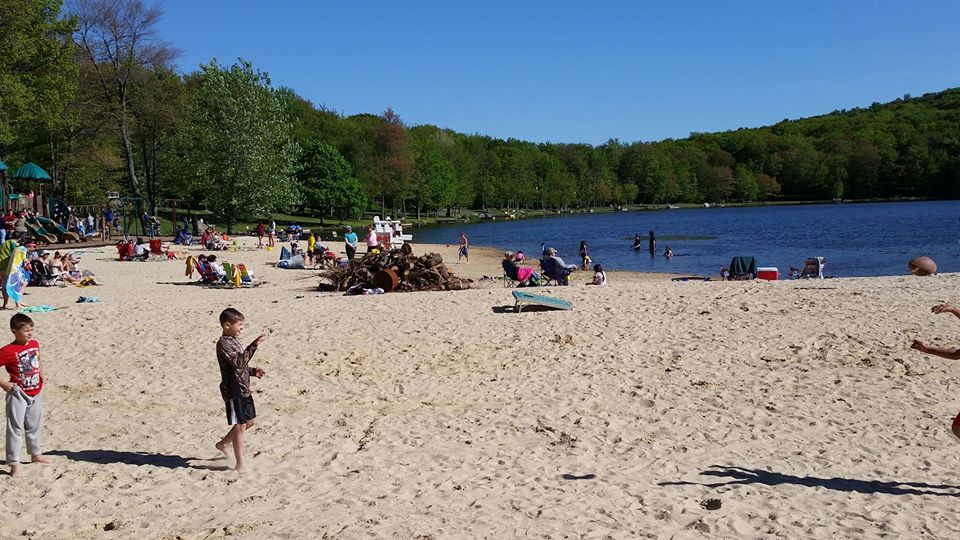 Community members sitting on the beach and swimming