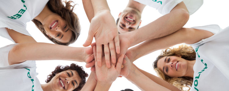Cheerful group of volunteers putting hands together on white background