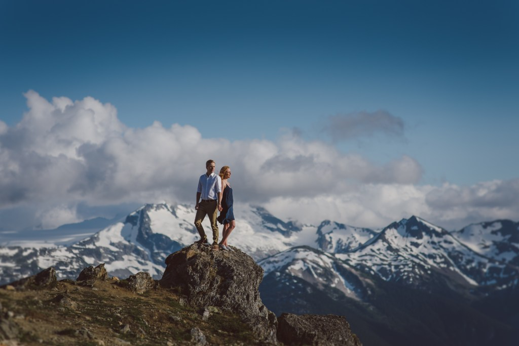An engaged couple on a rock with a view of the mountains in the distance