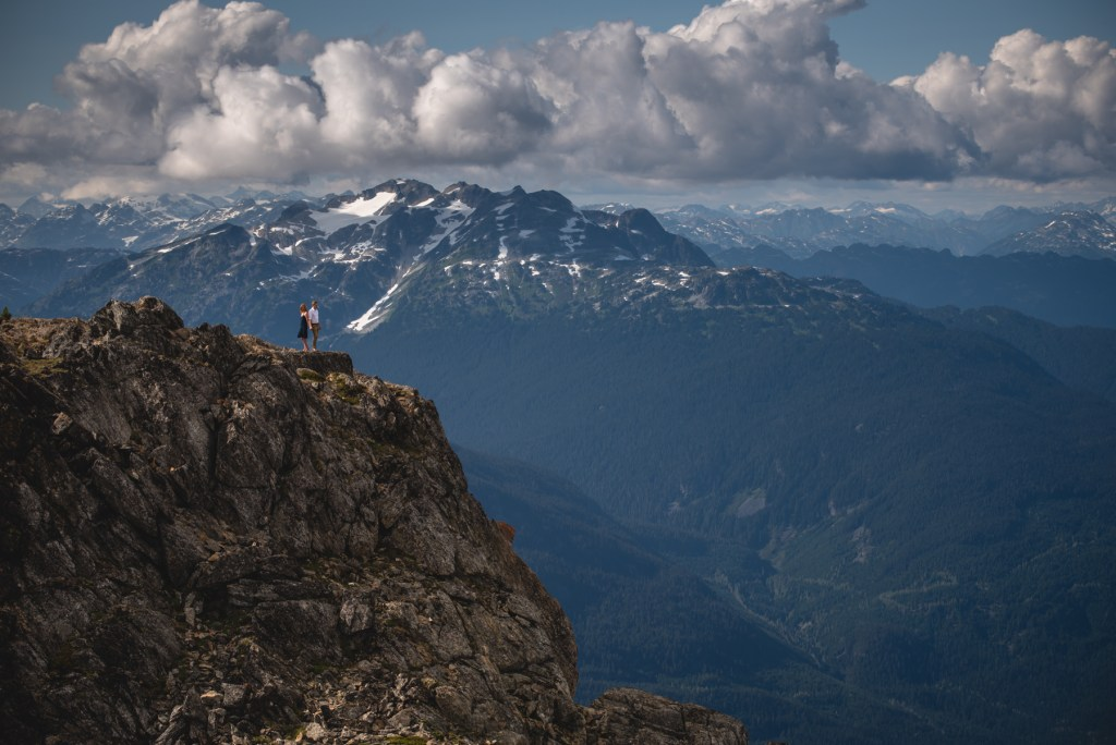 An engaged couple standing on the peak of Whistler Blackcomb