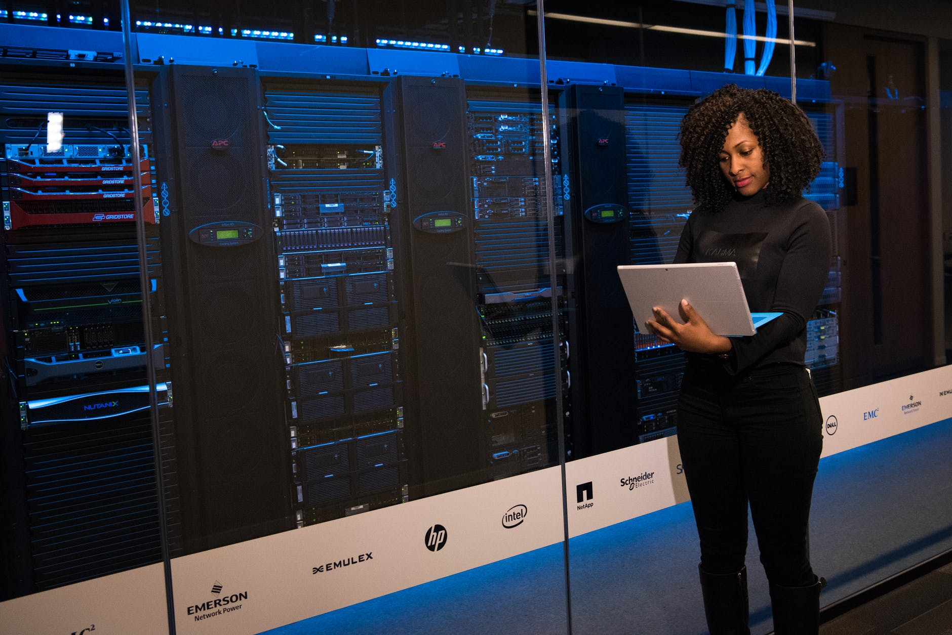 software engineer standing beside server racks