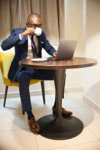 Man in blue suit working at laptop on table while drinking coffee