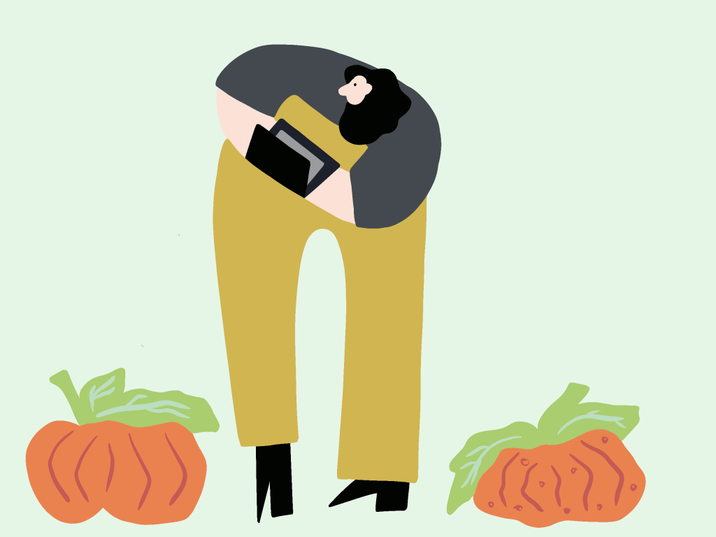 Illustration of a person using a laptop in front of pumpkins