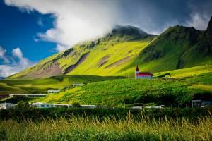 green field near mountain during daytime