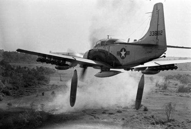 Flying low over the jungle, an A-1 Skyraider drops 500-pound bombs on a Viet Cong position below as smoke rises from a previous pass at the target, Dec. 26, 1964. (AP Photo/Horst Faas)