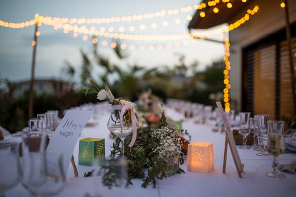 Décoration d'une table de mariage en extérieur avec guirlandes lumineuses