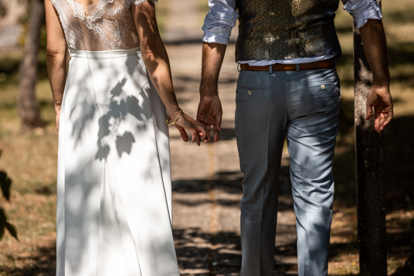 Les mariés marchent main dans la main de dos