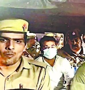 अजय को जेल ले जाते पुलिस वाले।