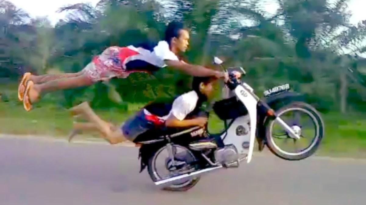 Dois jovens brincam em cima de uma mota a fazer manobras inacreditáveis