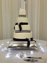 """""""Lauren"""" Square and round tiered wedding cake with navy and rhinestone ribbon accents."""