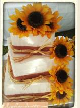 """""""April"""" Country Chic sporting burlap ribbon made of fondant, sunflowers, and straw."""