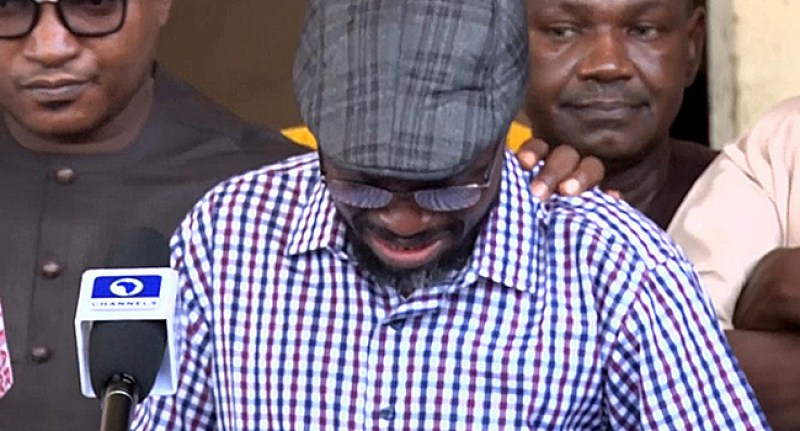 Bespectacled man in chequered shirt and cap crying in a press conference