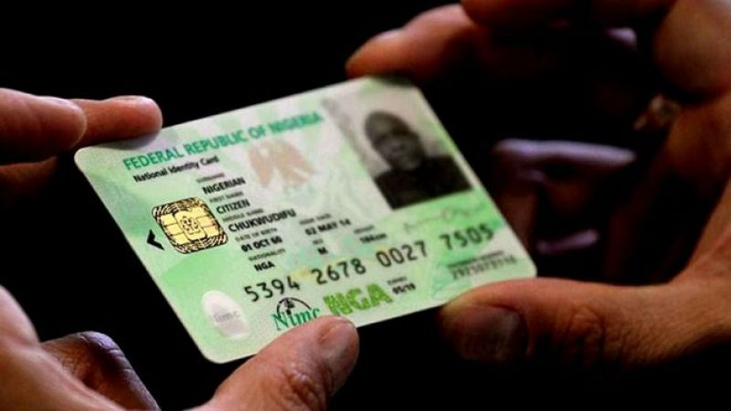 Thumb and index finger holding the Nigerian National Identity Card