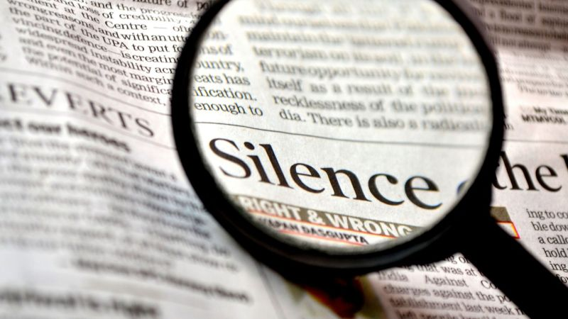 """Looking at the word """"Silence"""" in the newspaper through a magnifying glass"""
