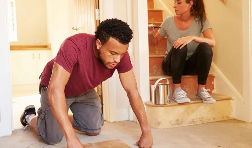 man and woman doing repairs to floor and walls of home