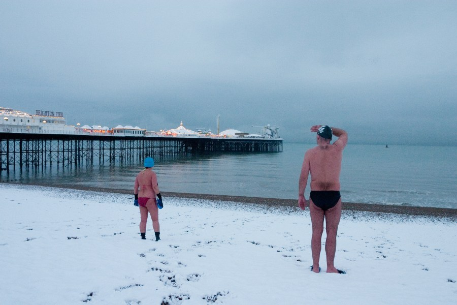 Two swimmers look out to sea on a snow covered beach