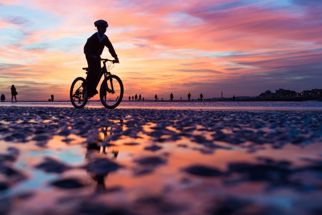 Cycling on Brighton beach at low tide by Kevin Meredith
