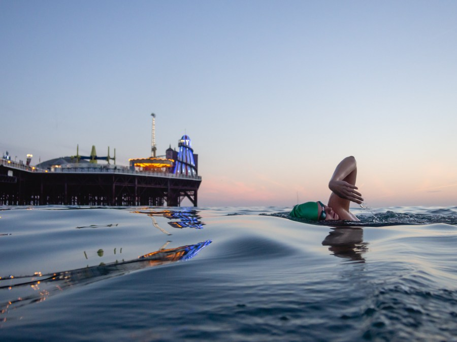 Member of Brighton Swimming Club Elle swimming near Brighton Pier at Dusk