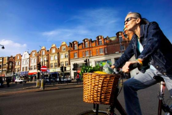 Woman cycles through street in London with blue sky in the background