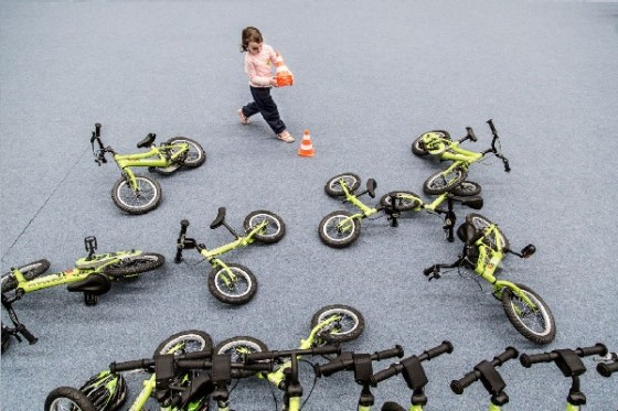Child playing with bikes and cones