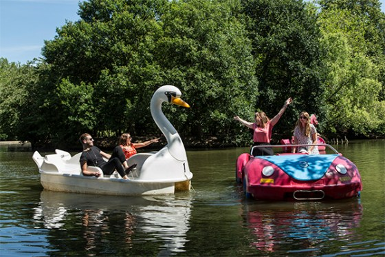 Group of people on two pedlows, one is a swan and one is a car.