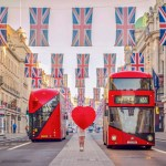 British flags above two red double decker buses and a girl with a red heart umbrella