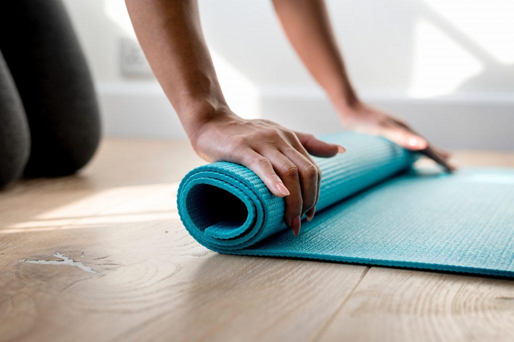 woman folding up a blue yoga mat on a wooden floor