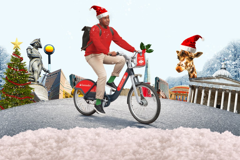 Image of a man riding a Santander Cycle in Christmas clothing