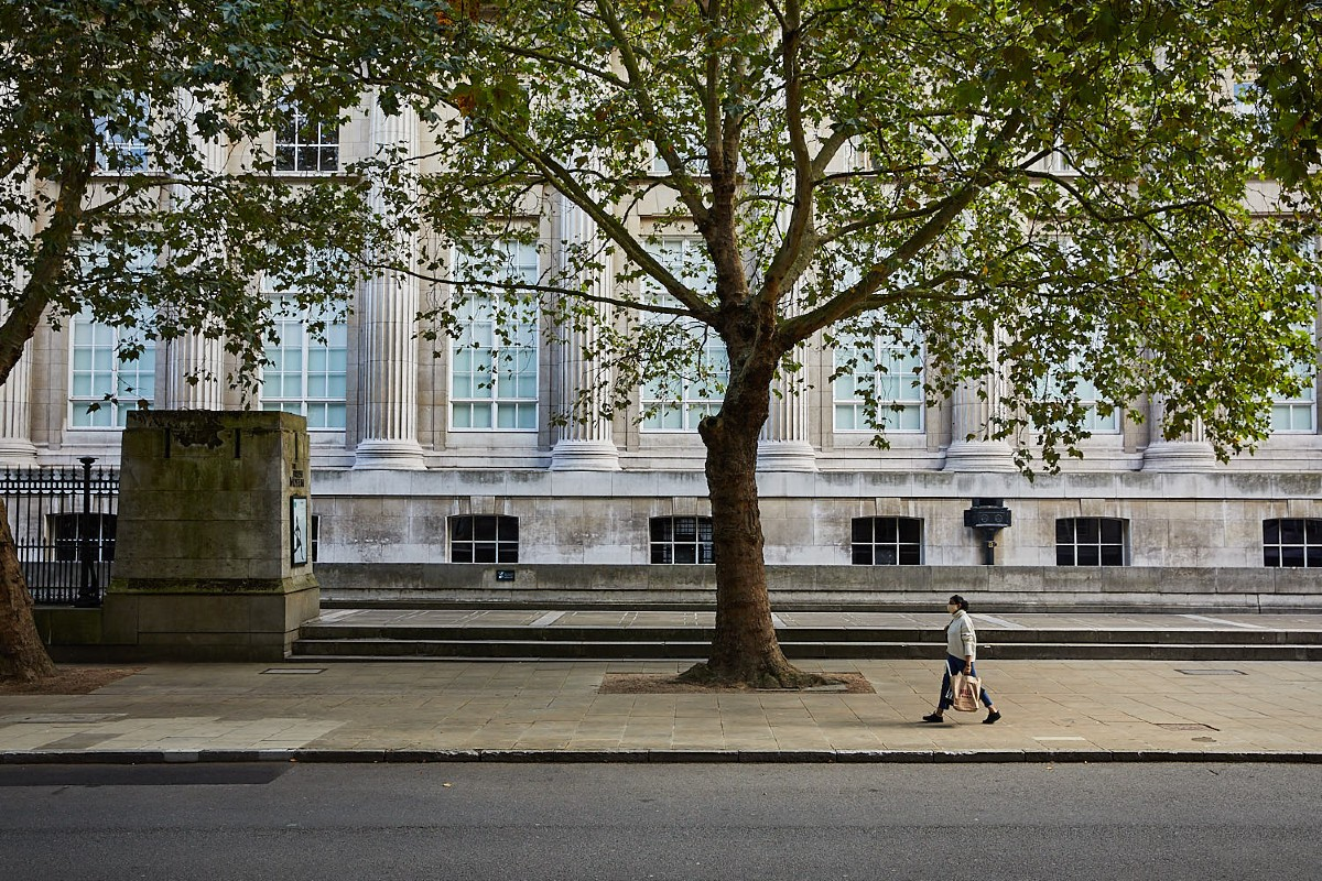 Person walking along the street outside the British Museum beside a tree