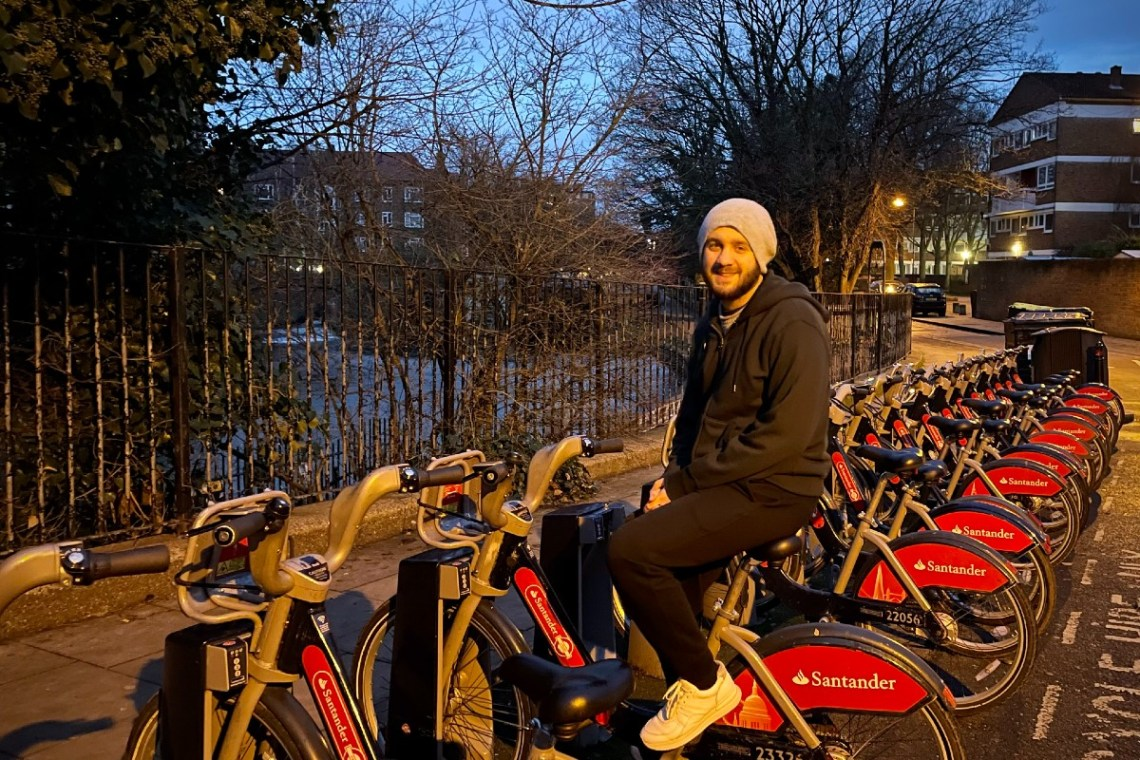 Matt at a Santander Cycles docking station in the evening