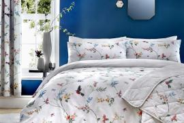 Blue painted wall with white flowery bedding