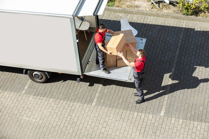 Male Movers Unloading The Cardboard Boxes Form TRemoval Van