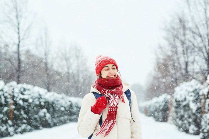 Women standing in snow wearing red scarf and hat.