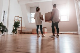Couple moving into new home. Holding boxes.