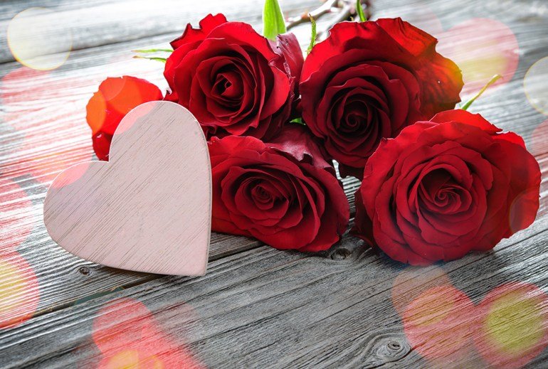 Bunch of red roses with wooden heart