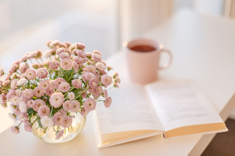 Small readig nook with pink flowers, drink and book