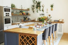 Stylish kitchen with moroccan tiles, central kitchen island and hanging plants